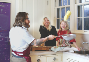Chef Jonathon Sawyer shows off his noodle cooking style as his wife Amelia and daughter Louisiana, 8, watch. Photography by Kim Stahnke